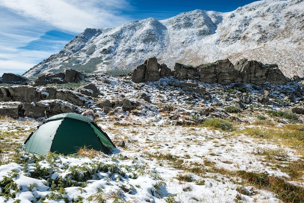Tente verte dans les montagnes de neige. beau paysage printanier