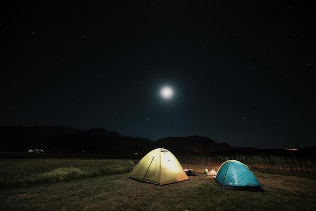 Tentes touristiques dans le camp parmi les prés dans les montagnes de nuit