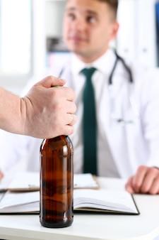 Tenue alcoolique dans la bouteille vide à la main à la réception du médecin