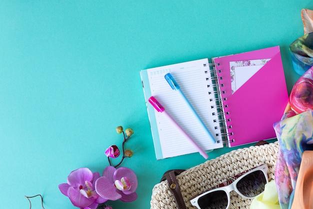 Tenue d'appartement de mode féminine d'été coloré. sac de paille, lunettes de soleil, branches de palmier, sur fond bleu, vue de dessus, composition large. mode d'été, concept de vacances