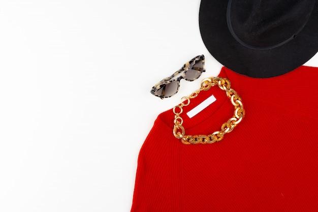 Tenue femme avec pull rouge et accessoires sur blanc