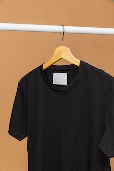 Tenue noire avec étiquette de vêtements espace copie sur cintre