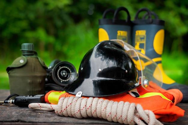 Tenue de pompier sur le vieux fond de table, concept de matériel d'incendie.