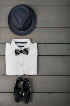 Tenue pour homme sur fond en bois, vêtements de mode pour enfants, fedora gris, chemise blanche, chaussures bateau pour garçon, vue de dessus, pose à plat, espace de copie.