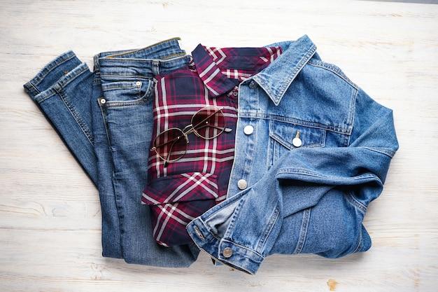Tenues décontractées pour femmes avec des vêtements en jean sur une surface en bois, à plat.