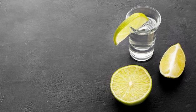 Tequila argent à angle élevé tourné avec des tranches de citron vert
