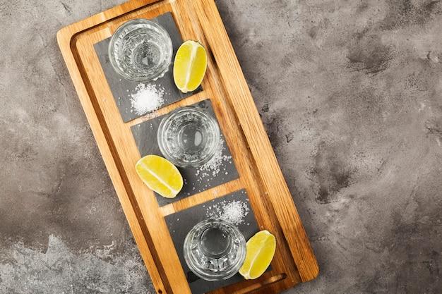 Tequila coups, limes et sel sur planche de bois sur un espace gris. vue de dessus, espace copie