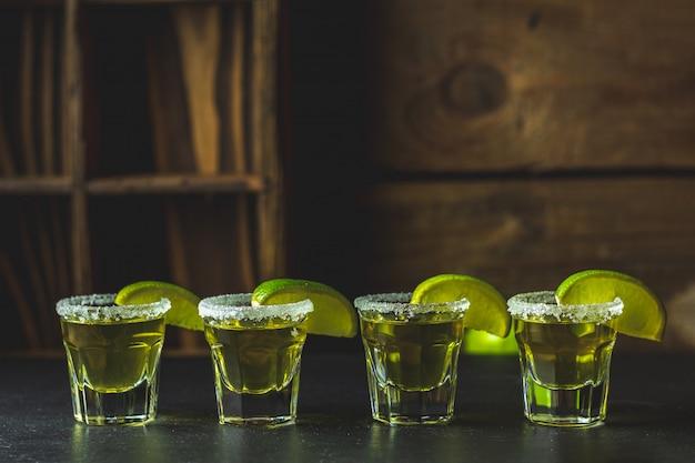 Tequila doré mexicain tourné au citron vert et au sel sur une table en pierre noire