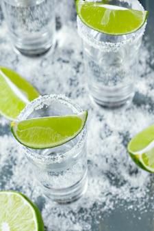 Tequila mexicaine dans des verres courts avec citron vert et sel
