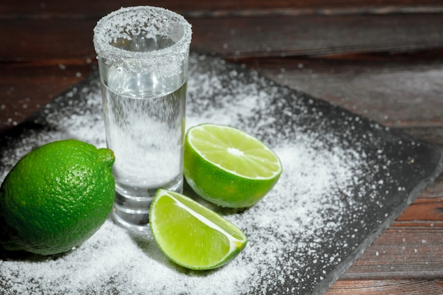 Tequila silver shots avec des tranches de citron vert et du sel sur une planche de bois