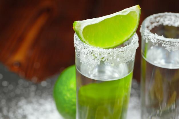 Tequila silver shots avec tranches de citron vert et sel sur planche de bois