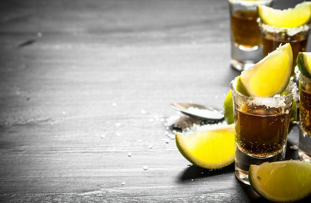 Tequila avec des tranches de sel et de citron vert. au tableau.