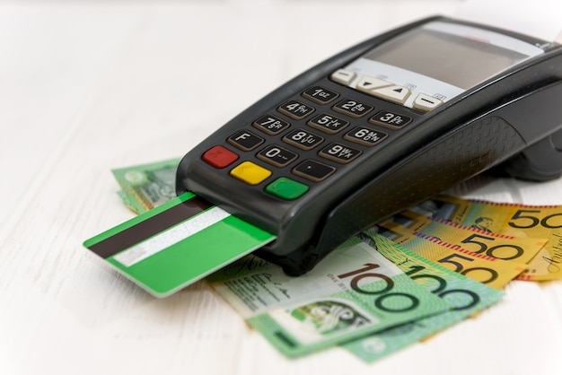 Terminal bancaire avec carte de crédit sur les billets en dollars australiens