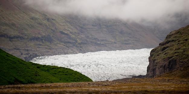 Terminus de glacier dans la vallée de montagne accidentée
