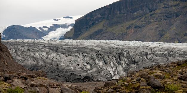 Terminus de glacier à travers la vallée de montagne