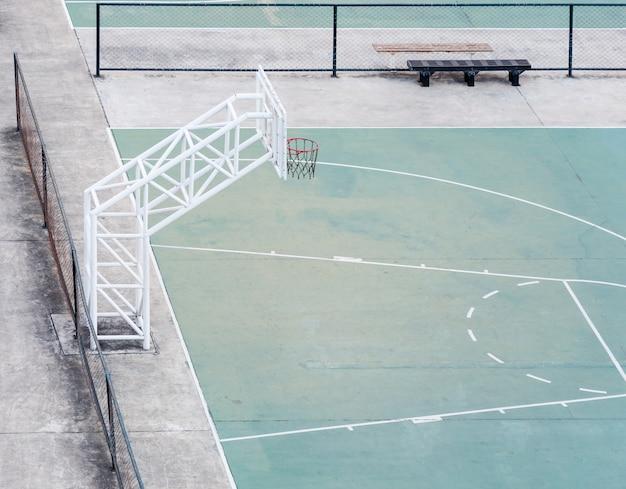 Terrain de basket vide avec l'ancienne clôture.