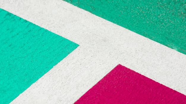 Terrain de basketball en béton vert et rose - gros plan