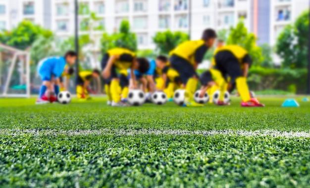 Terrain de football en arrière-plan, joueurs de football pour enfants s'entraînant sur le terrain