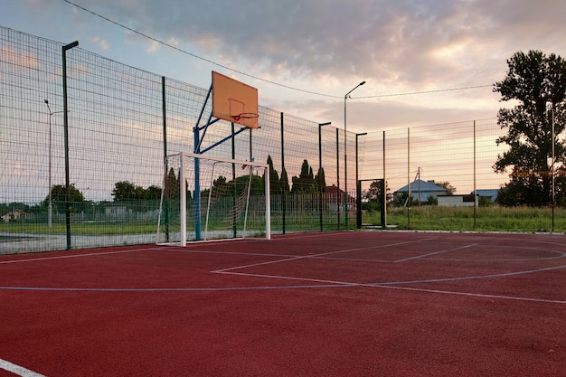 Terrain de football et de basketball extérieur avec porte de base-ball et panier entouré d'une haute barrière de protection.