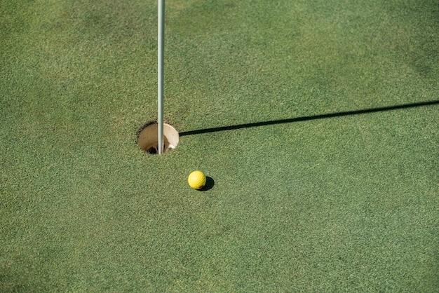 Terrain de golf avec balle jaune près du trou