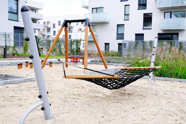 Terrain de jeu avec hamac et balançoire dans la cour confortable du quartier résidentiel moderne.