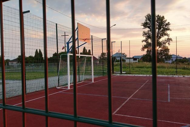 Terrain de mini-football et de basket-ball en plein air avec porte à billes et panier entouré d'une haute barrière de protection.