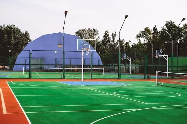Terrain de sport extérieur avec gazon artificiel pour jouer au tennis et au basket.