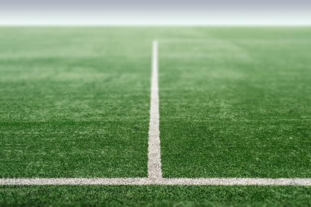 Terrain de sport vert avec gazon artificiel, perspective du terrain de football.