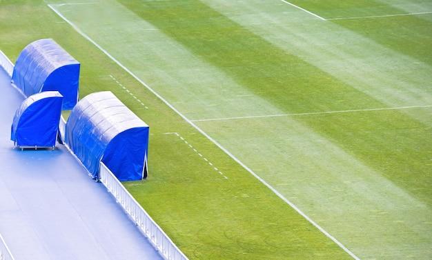Terrain vert de football football avec banc d'entraîneur sur le stade