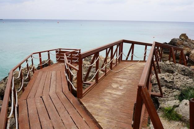 Terrasse en bois sur le rivage entouré de rochers et de mer sous un ciel nuageux