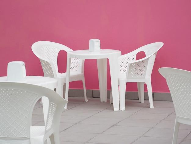 Terrasse de café en plein air avec mur rose, chaises et tables en plastique blanc.