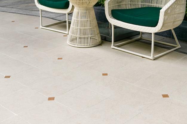 Terrasse extérieure avec carrelage au sol beige avec coin salon. revêtement de sol en carreaux de granit céramique. décoration de jardin.