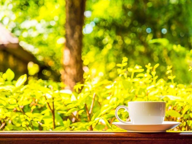 Terrasse extérieure avec vue magnifique sur la nature et tasse à café blanche
