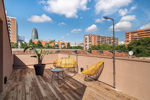 Terrasse lumineuse avec des chaises extérieures jaunes, une douche au sol en bois et une vue imprenable sur la zone de l'ancien quartier industriel de poblenou converti en nouveau quartier moderne à barcelone, espagne