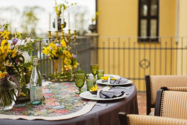 Terrasse de restaurant décorée et table servie avec des fleurs et des bougies pour un dîner romantique de mariage