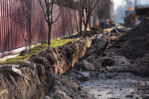 Terrassement. une longue tranchée profonde creusée dans le sol pour la pose de câbles, de tuyaux.