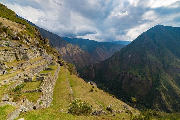 Les terrasses du machu picchu offrent une vue abrupte d'en haut sur la vallée d'urubamba
