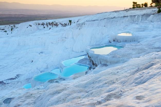 Terrasses en travertin naturel de pamukkale remplies d'eau bleue au coucher du soleil