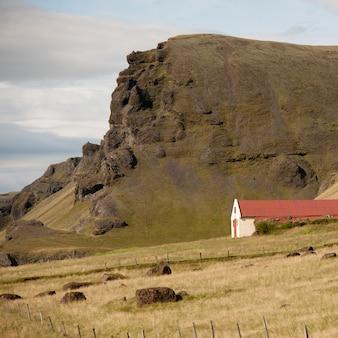 Des terres agricoles et une grange sous la falaise herbeuse