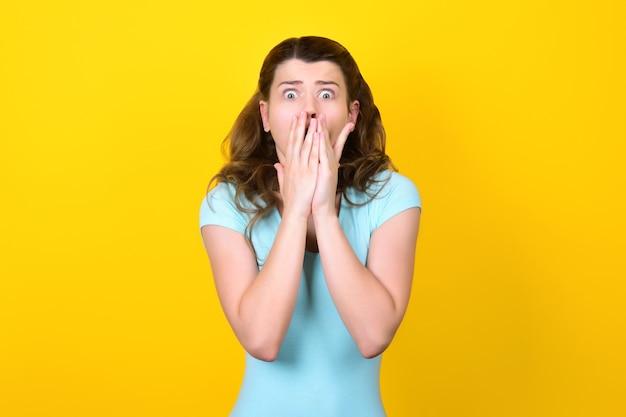 Terrifiée jeune femme aux yeux exorbités couvre sa bouche avec ses mains.