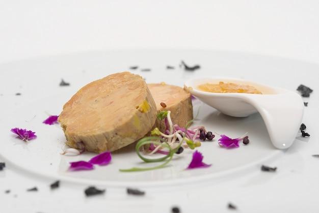 Terrine de foie servie avec une sauce sucrée, décorée de pétales de fleurs et de feuilles vertes