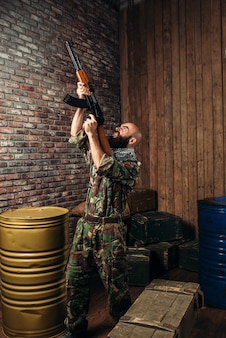 Terroriste barbu tenant le fusil kalachnikov. terrorisme et terreur, soldat en camouflage kaki