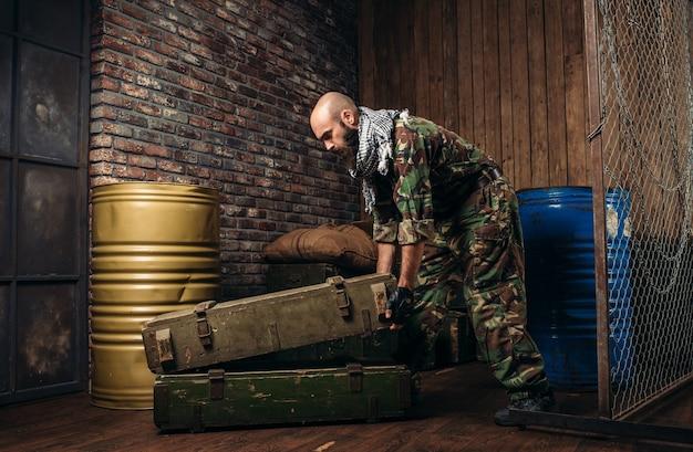 Terroriste en uniforme charge des boîtes de munitions. terrorisme et terreur, un soldat en tenue de camouflage reconstitue l'arsenal