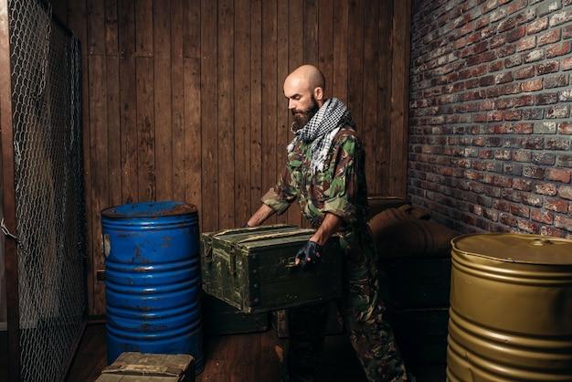 Terroriste en uniforme charge des boîtes de munitions