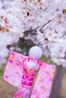 Teru teru bozu. poupée de pluie japonaise accrochée à un arbre sakura pour prier pour le beau temps