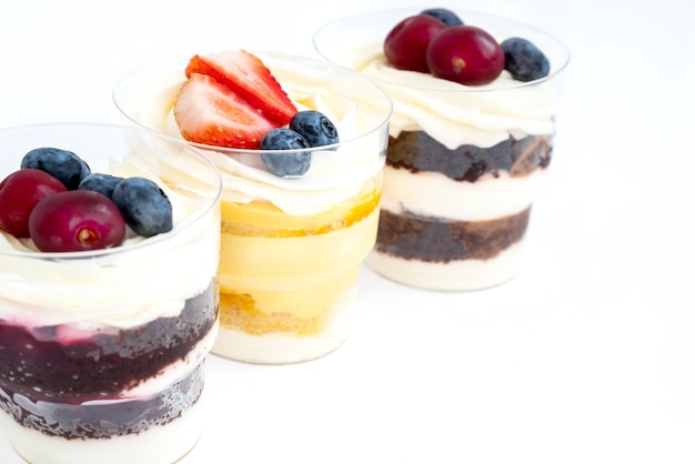 Tes portions de gâteaux sucrés décorés de baies fraîches d'affilée sur fond blanc