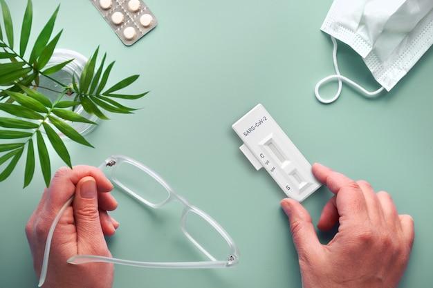 Test covid-19 rapide en main. table verte avec masque facial, pilules, palmier et lunettes. détection sérologique des anticorps igm et igg dirigés contre le nouveau coronavirus sars-cov-2.