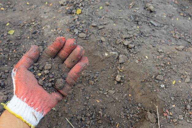 Test de l'échantillon de sol en main qui porte un gant avec un fond de sol. le concept de la qualité des sols et de l'agriculture