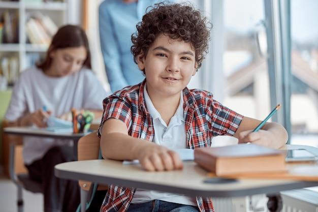 Test d'écriture mignon garçon bouclé assis au bureau dans la salle de classe.