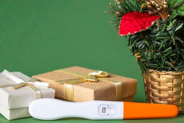 Test de grossesse positif avec coffrets cadeaux et arbre de noël.